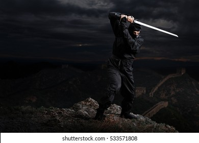 At night. Assassin ninja with sword on cliff waiting in ambush