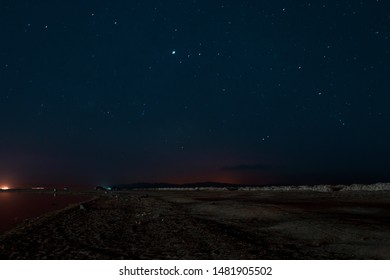 Night Astrophotography of Laguna Beach with the sky lit up by stars in Dahab, South Sinai, Egypt in the middle of the Red Sea desert.
