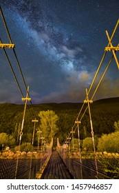 Night Astrophotography: Milky Way and clouds over Barruera suspension bridge in Pyrenees, Catalunya, Spain