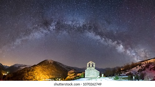 Night Astrophotography. Panoramic view of Milky Way over Sant Quirc of Durro Romanesque hermitage, Pyrenees,, Vall de Boi, Lleida, Catalonia, Spain