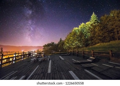 Night astrophotography: Panoramic view of Milky Way from a wooden platform. Nature landscape of mountain range and forest with universe space of milky way galaxy and stars on sky