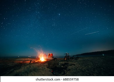 Night beach Bonfire under the stars with bikes in foreground