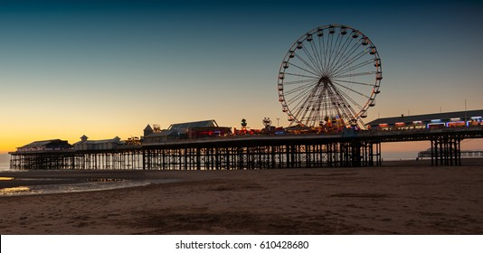 Night begins to fall and the neon lights are on illuminating the ferris wheel and other rides on central pier, blackpool , england