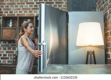 Night bite. Cheerful mature woman opening refrigerator and posing in profile