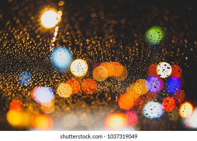 night bokeh on the road , with water drops on glass window