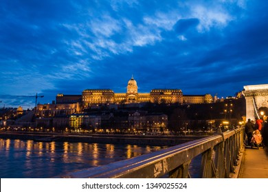 Night Budapest. Chain Bridge over Danube and illuminated historic Royal Palace aginst dark blue cloudy sky at dusk