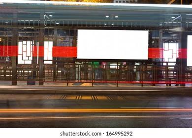 Night bus station with blank billboard