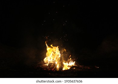 Night campfire in the winter forest. Sparks from the fire