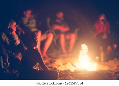 Night camping. Boy sitting near burning campfire and looking at the flame