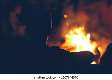 Night camping. Boy sitting near campfire and looking at the flame.