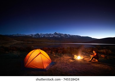 Night camping. Man tourists sitting in the illuminated tent near campfire under amazing sunset sky in a mountains area. Snow mountain in the background