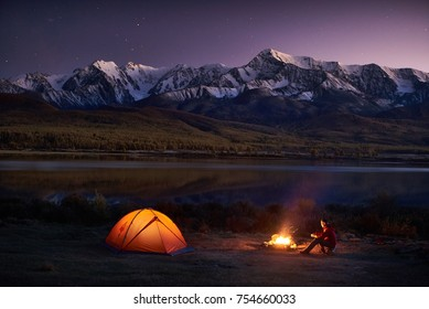 Night camping. Man tourists sitting in the illuminated tent near campfire under amazing sunset evening sky in a mountains area. Snow mountain in the background