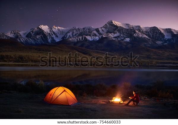 Nachtzelten. Viele Touristen sitzen im beleuchteten Zelt nahe dem Lagerfeuer unter erstaunlichem Sonnenuntergang abends Himmel in einem Gebirgsgebiet. Schneeberg auf Hintergrund