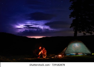 Night camping in the mountains. Couple tourists have a rest at a campfire near illuminated tent