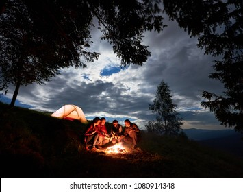 Night camping in the mountains. Group of friends hikers having a rest around campfire with beer, enjoying a holiday near glowing orange tent and forest under the cloudy sky at dawn