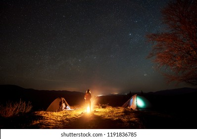 Night camping in mountains. Silhouette of female tourist standing between two tents at burning bonfire near big tree, enjoying deep dark sky with lot of bright stars. Tourism and travel concept
