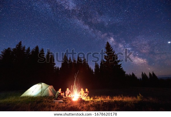 Night camping near bright fire in spruce forest under starry magical sky with milky way. Group of four friends sitting together around campfire, enjoying fresh air near tent. Tourism, camping concept.