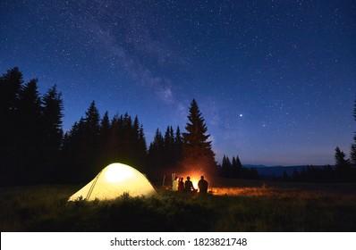 Nachtzelten in der Nähe von Feuer, Wald und Bergen auf dem Hintergrund. Gruppe von Freunden, die sich nahe hellem Feuer erwärmen. Menschen, die in der Nähe des touristisch beleuchteten Zeltes unter Nachthimmel voller Sterne und Milchstraße sitzen.