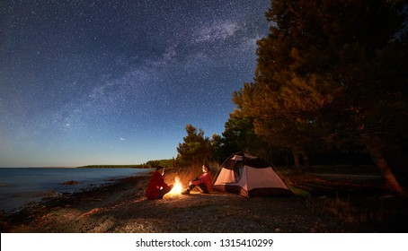 Night camping on shore. Young man and woman tourists sitting relaxed in front of tent at campfire under starry sky with Milky way on blue water and forest background. Active outdoor lifestyle concept