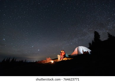 Night camping. Romantic couple tourists have a rest at a campfire near illuminated tent under beautiful night starry sky. Astrophotography