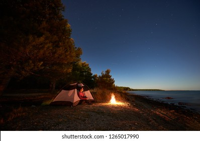 Night camping at sea. Pretty hiker girl resting in entrance of tent near forest at campfire under bright starry sky, enjoying beautiful view of clear blue water. Tourism, active lifestyle concept