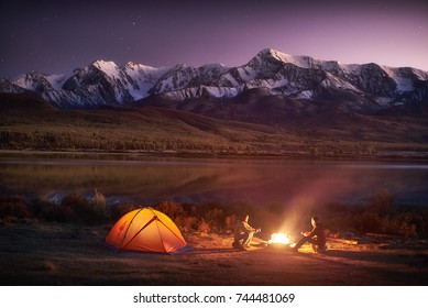 Night camping. Two men tourists sitting at the illuminated tent near campfire under amazing sunset evening sky in a mountains area. Snow mountain in the background