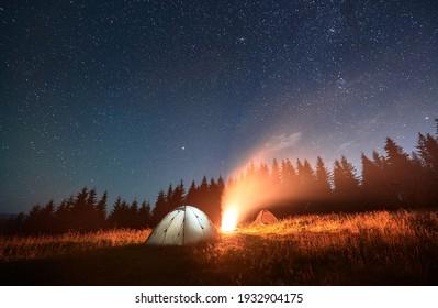 Nacht zelten unter erstaunlichem Sternenhimmel. Schöne Landschaft in den Bergen. Zwei beleuchtete Touristenzelte und Lagerfeuer, Fichtenwand auf Hintergrund. Konzept des Reisens und der Astrofotografie