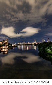 Night city buildings and clouds reflecting in the river water.