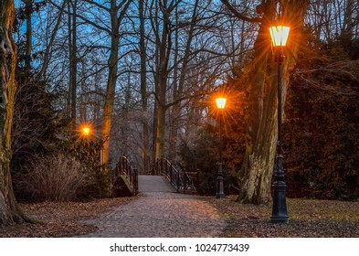 Night city landscape. Brick alley in the park in the lanterns lighting.