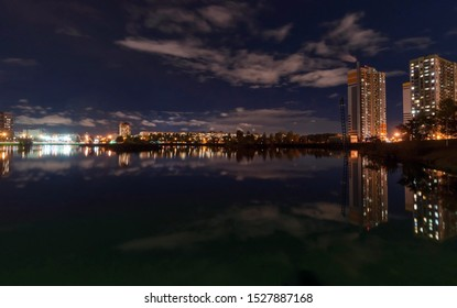 Night city landscape - high-rise houses with lighted windows on the shore of the pond, dark sky with clouds and reflection in the water