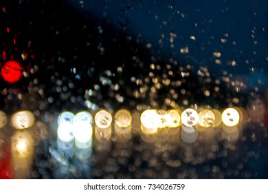 night city lights water drop on the obscured glass , raining drop and red blue color,  road light bokeh Abstract urban defocused background, rain drops on car window