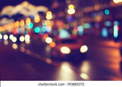 night city road background: defocused car headlights and street lamps, vintage colors