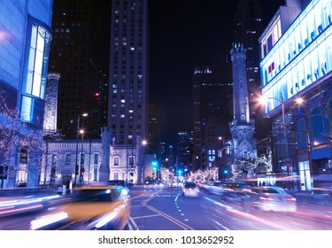 Night city scene in Chicago downtown in the street with light trails and Christmas lights on trees