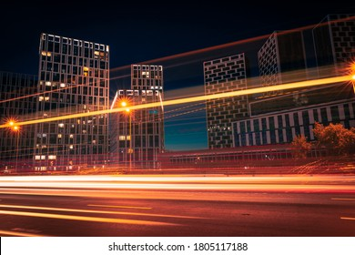 Night city street. Light trails from moving cars on the dusk urban road with modern buildings on the opposite side.