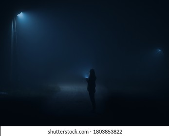 Night city in a thick wet fog . Film grain and noise. Silhouette of a girl with a flashlight walking along the road at night.