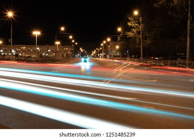 night city and traces of passing cars glowing lines from the headlights, in the background red glowing lines and a car with headlights on