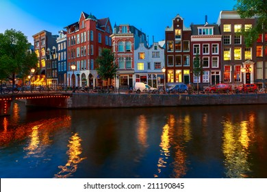 Night city view of Amsterdam canal, typical dutch houses and bridge, Holland, Netherlands.