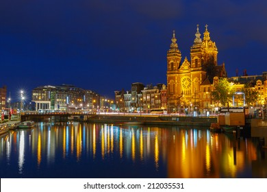 Night city view of Amsterdam canal and Basilica of Saint Nicholas, Holland, Netherlands. Long exposure.