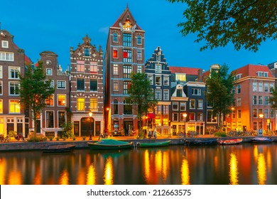 Night city view of Amsterdam canal Herengracht, typical dutch houses and boats, Holland, Netherlands.