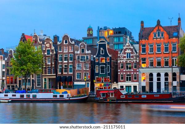 Nachtblick auf den Amsterdamer Kanal, typische Häuser und Boote, Holland, Niederlande.