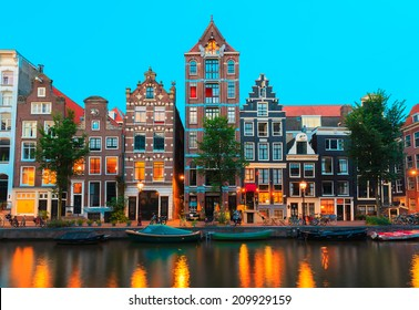 Night city view of Amsterdam canals and typical houses, boats and bicycles, Holland, Netherlands.