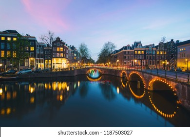 Night city view in Amsterdam, Netherlands. Canal and typical dutch houses at night in Amsterdam, Netherlands
