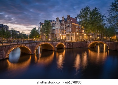 Night city view in Amsterdam, Netherlands. Canal and typical dutch houses at night in Amsterdam with the famous Canals