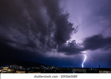night city view under thunderstorm with strike of lightning. Powerful thunderbolt during thunderstorm in the city. Cloud to ground electric lightning behind the city.