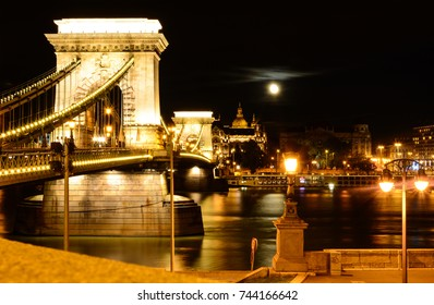 Night cityscape of Budapest with St. Stephen's Basilica, Danube river, Szechenyi Chain Bridge and full moon above the city
