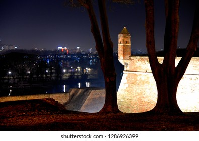 night cityscape from hill with old Kalemegdan fortress walls and city lights from Novi Beograd and Danube river in background in Belgrade, Serbia