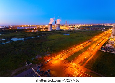 Night cityscape of industrial Saint-Petersburg, Russia.  Road with night light and power-and-heating with electric generation plant.