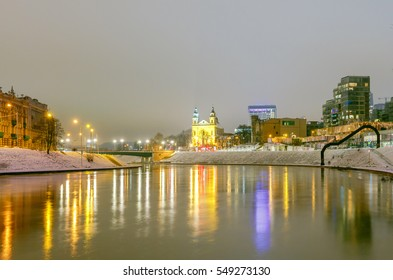 Night cityscape of the Neris River, Church and skyscrapers in the center of Vilnius at sunset. Lithuania.