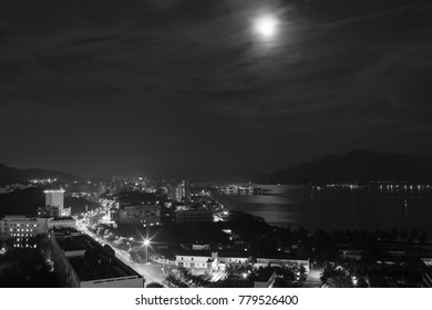 Night cityscape overlooking Dadonghai Bay in full moon - black and white
