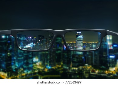 Night cityscape with skyscrapers and city lights as seen through a pair of glasses. Blurred image.